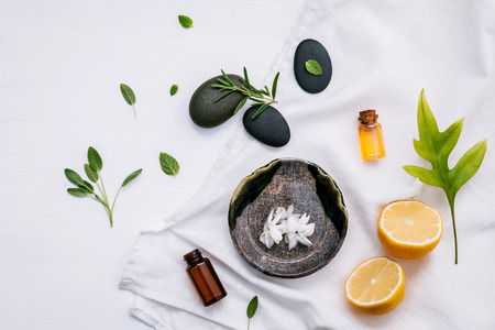 Alternative medicine and aromatherapy bottle of essential oil with fresh herbal sage, rosemary, lemon and peppermint setup with flat lay on white wooden table.