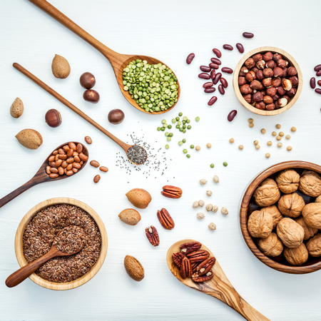 Bowls and spoons of various legumes and different kinds of nuts walnuts kernels ,hazelnuts, almond kernels,brown pinto ,soy beans ,flax seeds ,chia ,red kidney beans and pecan set up on white wooden table.