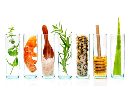 The glass bottle of homemade skin care and body scrubs with natural ingredients aloe vera ,himalayan salt ,peppermint ,rosemary,turmeric and honey isolate on white background.