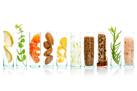Homemade skin care and body scrubs with natural ingredients aloe vera ,lemon,cucumber ,himalayan salt ,peppermint ,lemon slice,rosemary,almonds,ginger and honey pollen in glass bottles isolate on white background. Archivio Fotografico