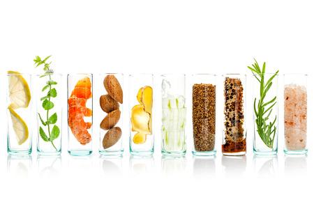 Zelfgemaakte huidverzorging en lichaam scrubs met natuurlijke ingrediënten Aloë vera, citroen, komkommer, Himalaya zout, pepermunt, schijfje citroen, rozemarijn, amandelen, gember en honing stuifmeel in glazen flessen isoleren op witte achtergrond.