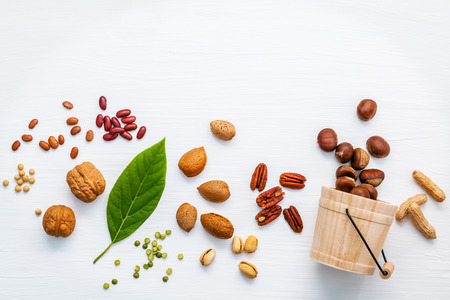 unsaturated: Selection food sources of omega 3 and unsaturated fats. Various legumes and different kinds of nuts walnuts kernels ,chestnuts, almond kernels,brown pinto ,soy beans ,peanuts ,red kidney beans and pecan set up on white wooden table.