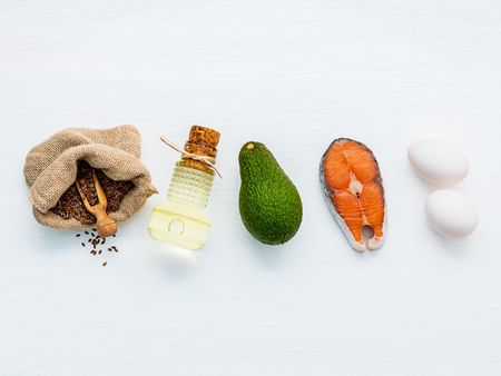 Olive oils ,salmon ,flax seeds ( linseed ) ,eggs and avocado on white wooden background. Archivio Fotografico