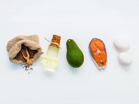 Olivenöl, Lachs, Leinsamen (Leinsamen), Eier und Avocado auf weißen Holz Hintergrund. Standard-Bild - 65511919