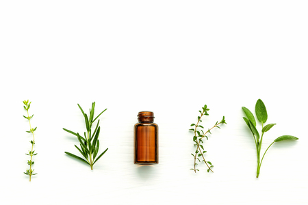 Bottle of essential oil with fresh herbal sage, rosemary, lemon thyme and thyme setup with flat lay on white wooden table.