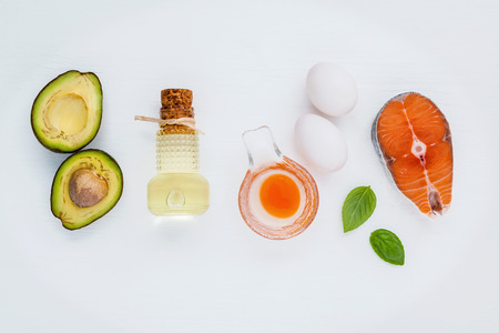 unsaturated: Selection food sources of omega 3 . Super food high omega 3 and unsaturated fats for healthy food. Olive oils ,salmon ,eggs and avocado on white wooden background. Stock Photo