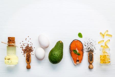 Aceites de oliva, salmón, semillas de lino (linaza), semillas de chia, huevos y aguacate sobre fondo blanco de madera.