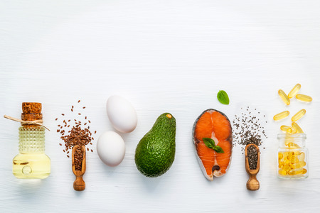 Olive oils ,salmon ,flax seeds ( linseed ) ,chia seeds,eggs and avocado on white wooden background.