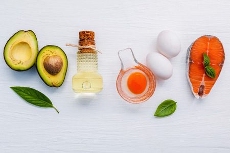 extra virgin: Halve avocado ,extra virgin olive oils ,white eggs and salmon fillets on white wooden background. Stock Photo