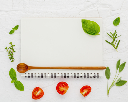 Notebook background for recipes and shopping list. Notebook ,sweet basil, peppermint ,cherry tomatoes slice and fork on white shabby wooden background . Archivio Fotografico