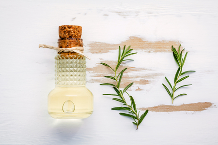 Sprigs of rosemary and olive oil set up on white shabby wooden background