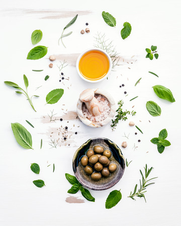 Different sorts of cooking oils. Olive oil flavored ,spice oils and sesame oil with herbs rosemary ,thyme,dill,sage ,peppermint ,oregano , sweet basil and parsley setup with shabby wooden background . Stock Photo