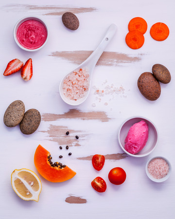 Homemade skin care and body scrubs with red natural ingredients strawberry ,tomato ,himalayan salt, papaya, carrot and spa stone setup on white wooden background Stock Photo