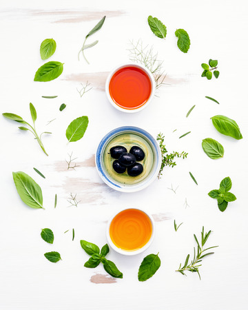 Olive oil flavored ,spice oils and sesame oil with herbs rosemary ,thyme,dill,sage ,peppermint ,oregano , sweet basil and parsley setup with shabby wooden background .