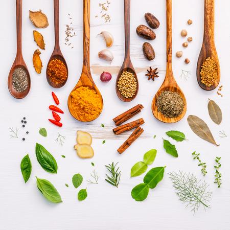 Plat van kruiden ingrediënten chili, peper, knoflook, droogt tijm, kaneel, steranijs, nootmuskaat, rozemarijn, basilicum en kaffir kalk op houten achtergrond.