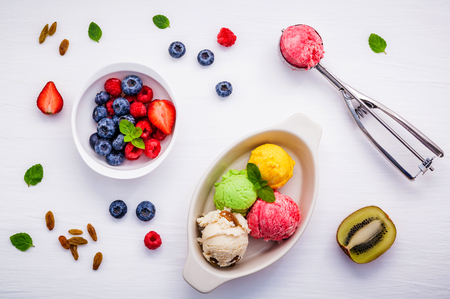 peppermint cream: Colorful ice cream with mixed berry raspberry ,blueberry ,strawberry ,halved kiwi and peppermint setup on white background
