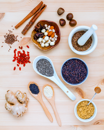 Nutritious Foods and Super foods selection with supplement powders in mortar and spoons setup on wooden background. Chia seeds ,flex seeds ,ginger ,rice berry ,sesame lotus seeds and mixed nuts. Stock Photo