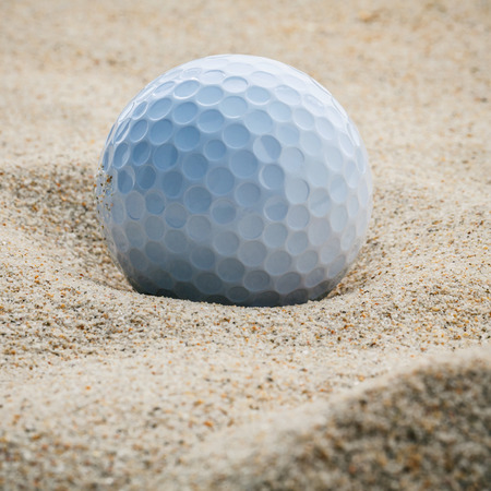 drawback: Close up golf ball in sand bunker shallow depth of field. A golf ball plugged deep in sand trap.