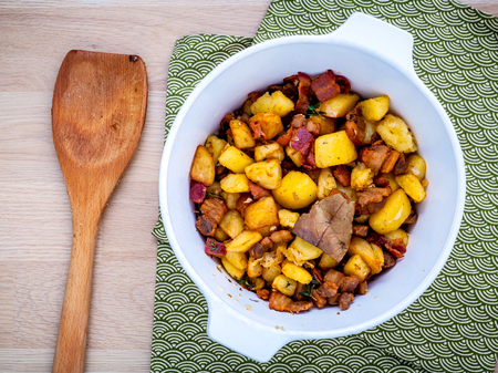 pancetta cubetti: French cuisine Lardons - Fried cubed pork belly , bacon and cubed potato with thyme ,bay leaves and galic  in a white bowl set up on wooden table flat lay.