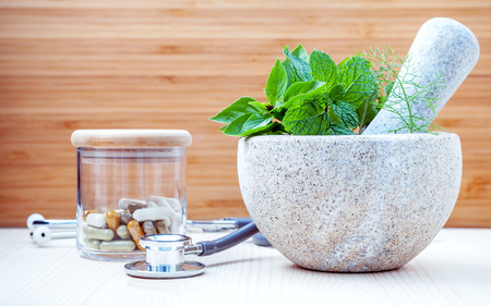 Alternative health care and herbal medicine .Fresh herbs and herbal capsule with mortar and pestle. Various herbs rosemary ,sage ,sweet basil and mint with stethoscope setup on wooden background.