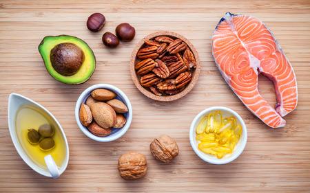 Selectie voedsel bronnen van omega 3 en onverzadigde vetten. Super eten hoge vitamine E en voedingsvezels voor een gezonde voeding. Almond, pecannoten, hazelnoten, walnoten, olijfolie, visolie, zalm op de snijplank. Stockfoto