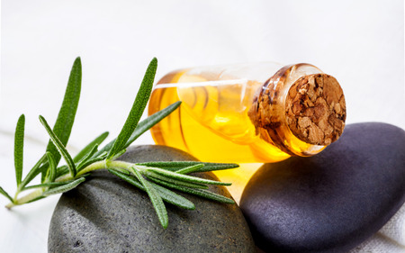 Alternative health care and herbal medicine . Close Up fresh rosemary leaves on spa stone with essential oil bottle setup on white wooden table. Selective focus shallow depth of field. Stock Photo