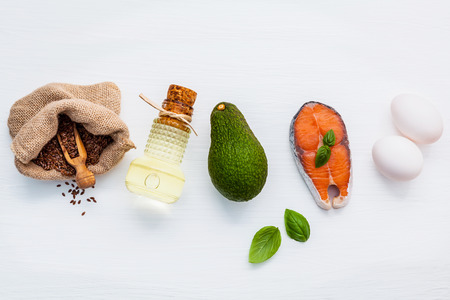 Selection food sources of omega 3 and unsaturated fats. Super food high vitamin e and dietary fiber for healthy food. Flax seed in hemp sack bag,olive oil ,fish oil ,salmon and white eggs on white wooden background. Stock Photo