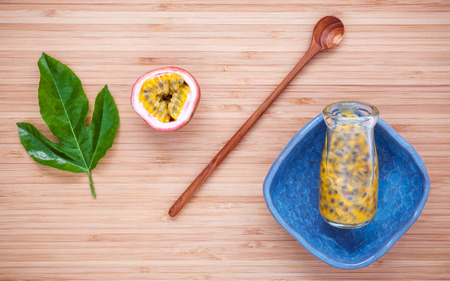 Fresh passion fruits  juice in bottle on bamboo background. Juicy passion fruits with  passion fruit leaves and wooden spoon flat lay on cutting board.