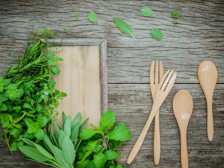 芳香のハーブやスパイスのフェンネル、オレガノ、セージ、レモンタイム、粗末な木製の背景にスプーンとフォークのペパーミント。健康食品のコ