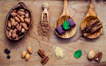 chocolate powder: Desserts background. Chocolate powder in scoop. Roasted cocoa beans in cocoa pod ,sugar ,coffee ,almonds ,pecan ,cinnamon,mint and dark chocolate bar setup on wooden background.
