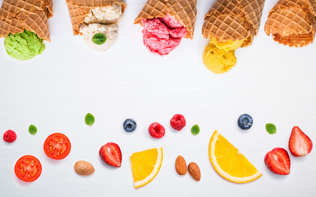 peppermint cream: Colorful ice cream with cones and various fruits raspberry ,blueberry ,strawberry ,almonds and peppermint leaves setup on white background . Summer and Sweet menu concept flat lay and copy space .