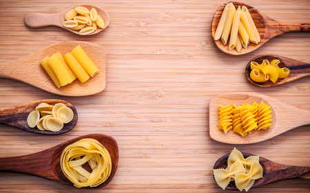 recipe background: Italian foods concept and menu design . Various kind of Pasta Elbow Macaroni ,Farfalle ,Rigatoni ,Gnocco Sardo in wooden spoons setup on bamboo cutting board with flat lay.