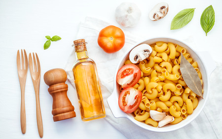 Italian foods concept and menu design . Pasta elbow macaroni  with ingredients sweet basil ,tomato ,garlic ,extra virgin olive oil ,parsley ,bay leaves and champignon setup on white background  flat lay .