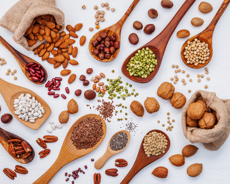 nutshells: Various kind legumes and nutshells in spoons and hemp sack bags. Walnuts kernels ,hazelnuts, almond ,brown pinto ,soy beans ,flax seeds ,chia ,red kidney beans and pecan set up on white wooden table.