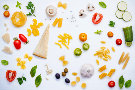 Italian food concept .Various kind of pasta with ingredients sweet basil ,tomato ,garlic ,parsley ,pine nut,pepper ,champignon ,zucchini and parmesan cheese on white wooden background flat lay. Stock Photo