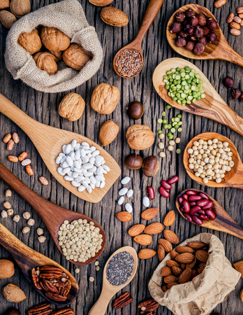 nutshells: Various legumes and different kinds of nutshells in spoons. Walnuts kernels ,hazelnuts, almond ,brown pinto ,soy beans ,flax seeds ,chia ,chickpea ,red kidney beans and pecan on shabby wooden table.