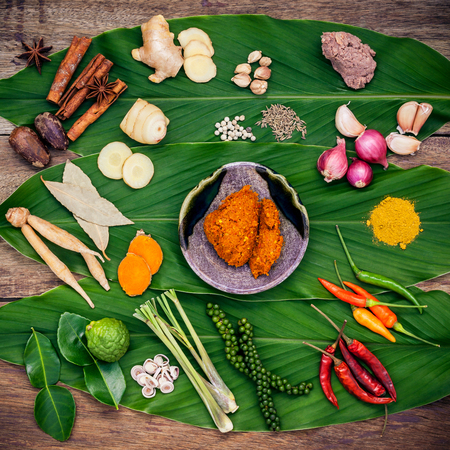 Various of Thai food Cooking ingredients and spice red curry paste ingredient of thai popular food on turmeric leaf background. Spices ingredients chili ,pepper, nutmeg, garlic and Kaffir lime leaves.
