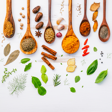Various herbs and spices in wooden spoons. Flat lay of spices ingredients chilli ,pepper, garlic,dries thyme, cinnamon,star anise, nutmeg,rosemary, sweet basil and kaffir lime on wooden background.