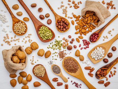 Various legumes and different kinds of nuts in spoons. Walnuts kernels ,hazelnuts, almond ,brown pinto ,soy beans ,flax seeds ,chia ,red kidney beans and pecan set up on white wooden table. Banco de Imagens