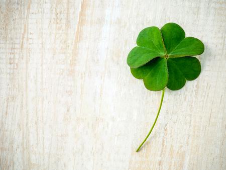 ぼろぼろの木製の背景にクローバーを残します。4 つ葉のクローバー最初の象徴的な信仰は、希望、2 番目、3 番目は愛、4 番目は、運。