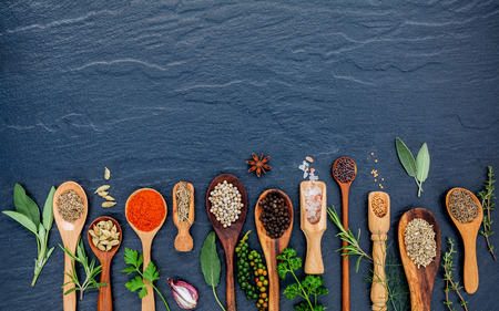 Various of spices and herbs in wooden spoons. Flat lay of spices ingredients chilli ,pepper corn, garlic, thyme, oregano, cinnamon, star anise, nutmeg, mace, sage and parsley on the black stone.
