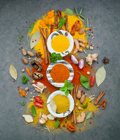 Various of spices and herbs in ceramic bowl. Flat lay of spices ingredients chilli ,pepper corn, garlic, oregano, cinnamon, star anise, nutmeg, mace, ginger and bay leaves on dark stone background.