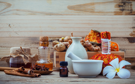 Natural Spa ingredients and herbal compress ball for alternative medicine and relaxation. Thai Spa theme with ayurvedic therapist on shabby wooden background. Archivio Fotografico
