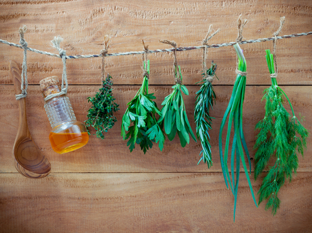 Various herbs hanging on shabby wooden background. Parsley ,sage,rosemary, fennel, shallot, thyme and essential bottles for seasoning concept. Stok Fotoğraf