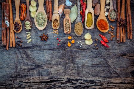 スパイスと木製のスプーンでハーブの様々 な。香辛料成分の唐辛子、唐辛子トウモロコシ、ニンニク、タイム、オレガノ、シナモン、スターアニス