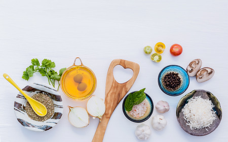 Various vegetable and ingredients for cooking pasta menu sweet basil ,tomato ,garlic ,extra virgin olive oil ,parsley  and champignon setup on white wooden background with copy space.