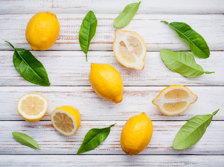 Fresh lemons and  lemons leaves on rustic wooden background. Fresh lemons and lemon slice on wooden table with flat lay.  Fresh citrus fruit background. Imagens