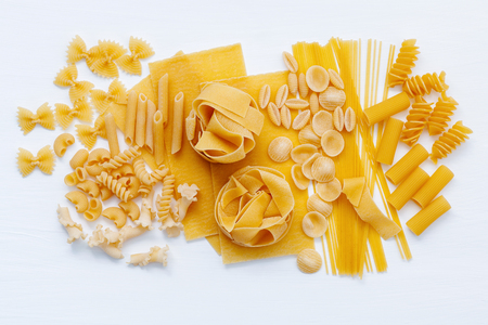 Italian foods concept and menu design. Assorted types of pasta Farfalle, Pasta A Riso, Orecchiette Pugliesi, Gnocco Sardo and Farfalle  setup on white wooden background with flat lay.