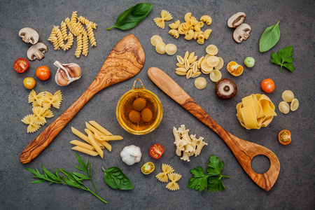 Italian foods concept and menu design. Fettuccine with wooden spatula and ingredients sweet basil ,tomato ,garlic ,parsley ,champignon and extra virgin olive oil setup on dark stone background. Stock Photo