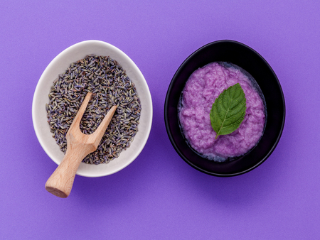 Homemade skin care lavender bath salt beauty treatment, peppermint leaves and lavender flower on purple background flat lay.